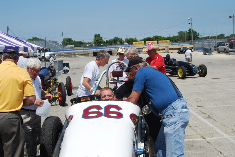 Natenshon (on right side of car) directs Jim Rugowski on how to get the disabled boy buckled into the vintage racing car.